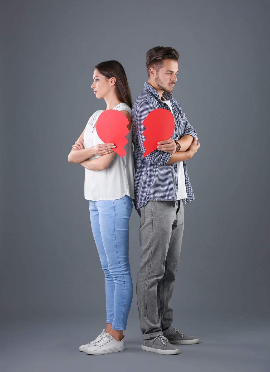 Young couple with torn paper heart on grey background. Relationship problems